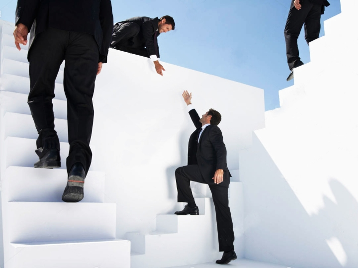 businessmen-climbing-stairs-moving-down-and-helping-another-man-to-climb-XD6RAM
